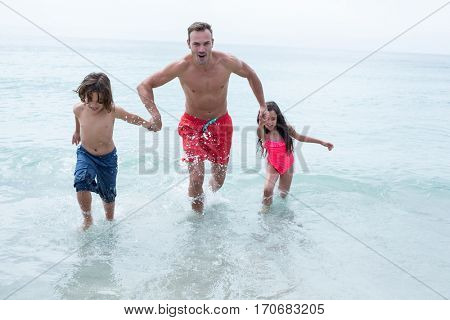 Happy father running with children at beach against sky