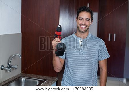 Portrait of happy man holding cordless hand drill at home