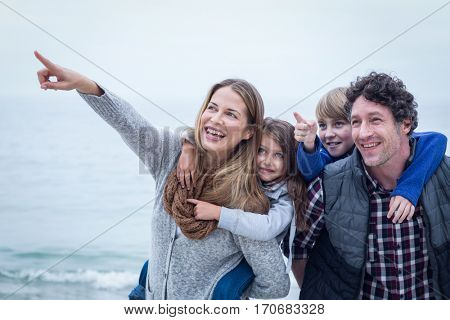 Cheerful mother pointing while enjoying with family at beach