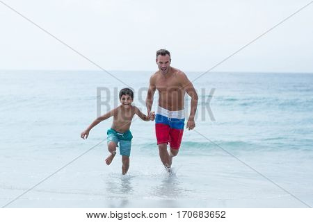Full length of father and son running on sea shore at beach