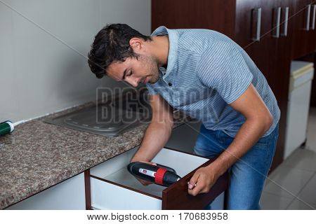 Man using cordless hand drill while bending at home