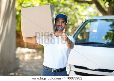 Portrait of smiling delivery man showing thumbs up while standing by van