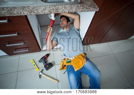 High angle view of man fixing sink pipe in kitchen