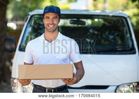Portrait of cheerful delivery person holding cardboard box while standing by van