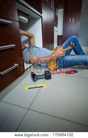 Midsection of man holding hammer while working in kitchen