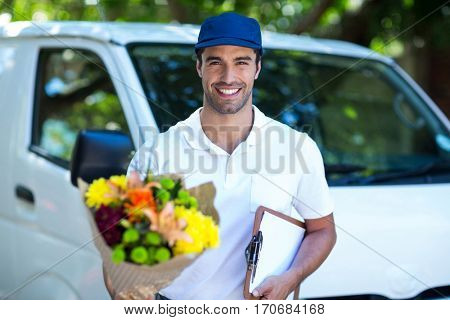 Portrait of smiling delivery man holding flower bouquet and clipboard while standing by van