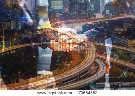Double Exposure of Business People join hand as Teamwork United and Urban Expressway or Autobahn at night as Business Teamwork concept