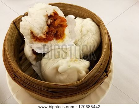 Chinese food in China town BBQ pork stuff steam bun on the bamboo basket bamboo tray in the local traditional Chinese restaurant with blur background table