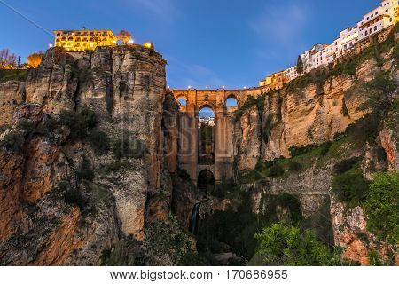 The popular historic landmark of spectacular Puente Nuevo, New Bridge, at dusk over Guadalevin River in town of Ronda, Andalusia, Spain.