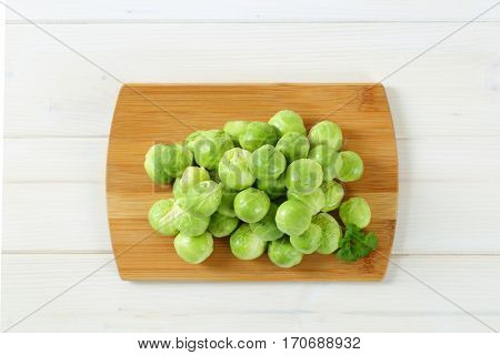 heap of raw Brussels sprouts on wooden cutting board