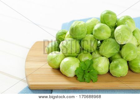 heap of raw Brussels sprouts on wooden cutting board - close up