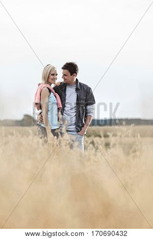 Happy loving young couple standing together at field