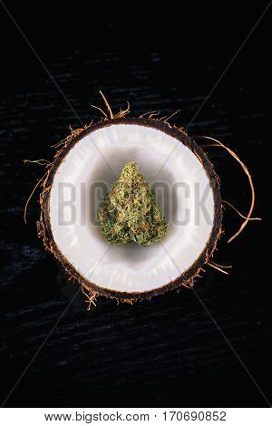 Detail of dried cannabis bud inside an opened coconut half isolated on black - medical marijuana concept