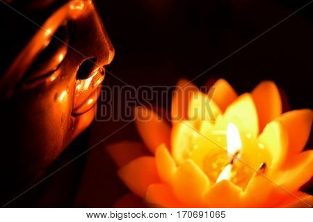 Buddha head in profile, illuminated by a candle in the form of a lotus flower.