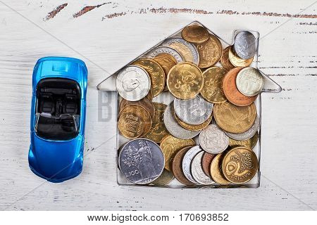 Coins in house-shaped form, car. Shopping on a grand scale.