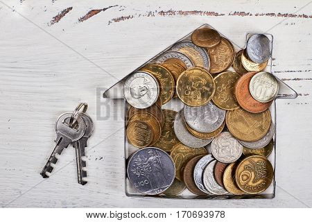Coins in house-shaped form, keys. Purchase of dream.