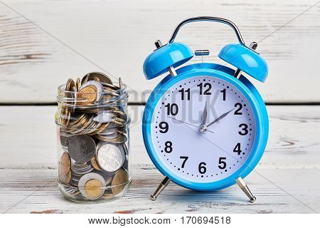 Alarm clock and coins. Time to make credit payment.