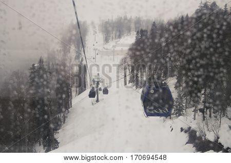 Sochi, Russia - 1 January, Raindrops on glass cabin cableway, 1 January, 2017. Winter mountain ski resort Rosa Khutor.