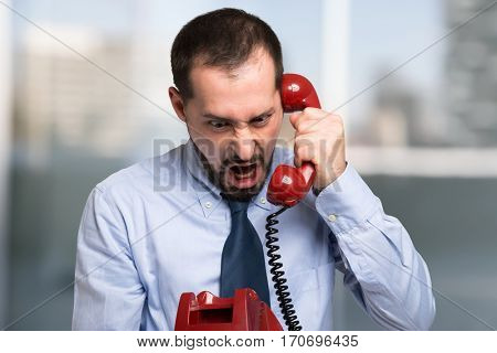 Angry businessman yelling on the phone