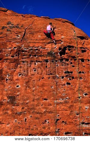 Rock climbing on red sandstone for sport recreation challenge and fun