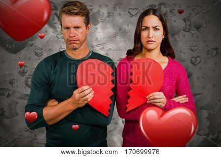 Portrait of serious couple holding cracked heart shape against love heart pattern 3d