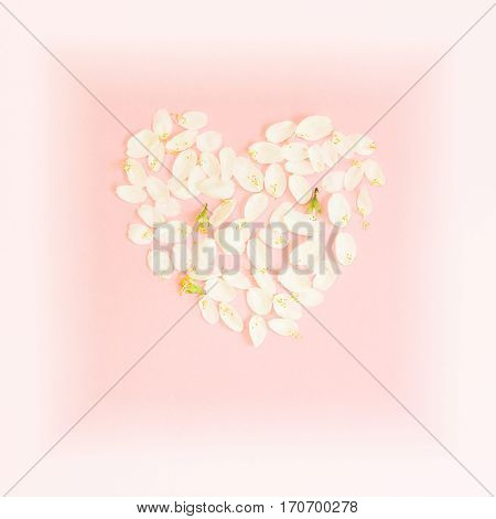Delicate Valentine background with heart made of petals. Heart of rose petals on a pink background.