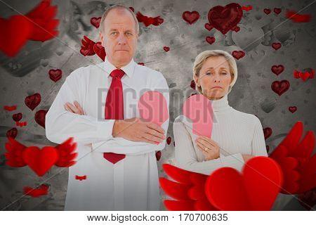 Older couple standing holding broken pink heart against love heart pattern