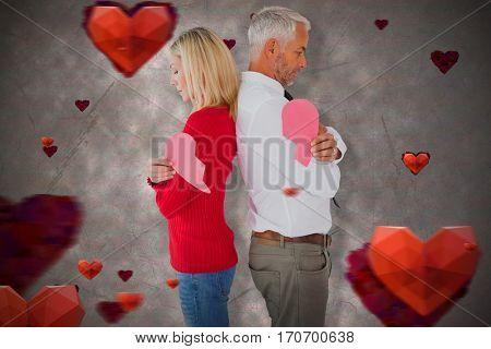 Couple holding two halves of broken heart against love heart pattern