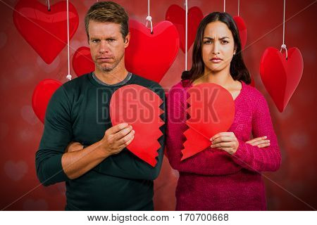 Portrait of serious couple holding cracked heart shape against valentines heart design 3D