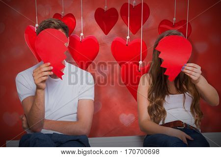 Couple holding broken heart against valentines heart design 3d