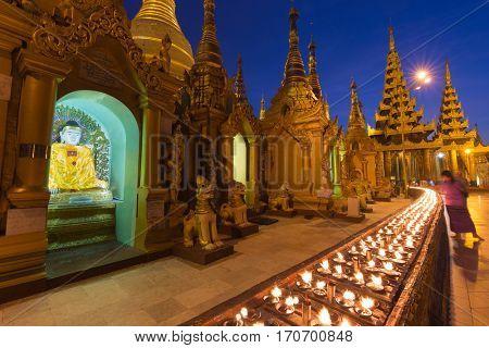Night scene at Shwedagon Pagoda in Rangoon with aligned candles, Myanmar