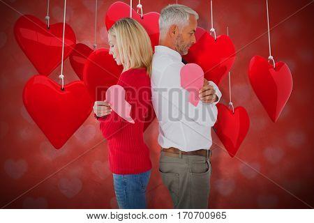 Couple holding two halves of broken heart against valentines heart design 3d