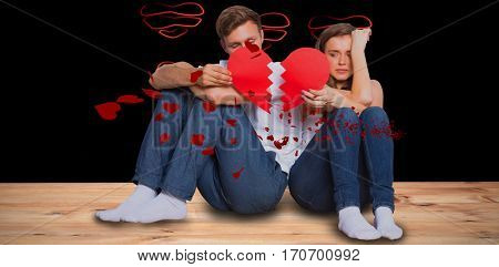 Young couple holding broken heart against red hearts floating