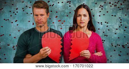 Portrait of serious couple holding cracked heart shape against blue paint splashed surface