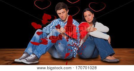 Young couple sitting on floor with broken heart against red hearts floating