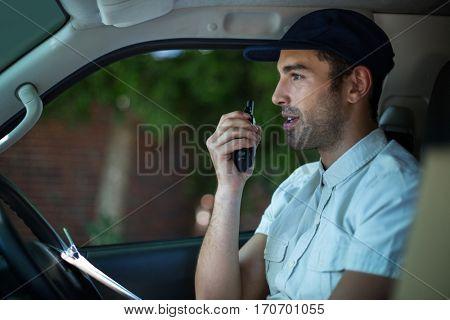 Delivery man using walkie-talkie while sitting in van