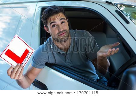 Portrait of handsome man shrugging while holding L plate in car