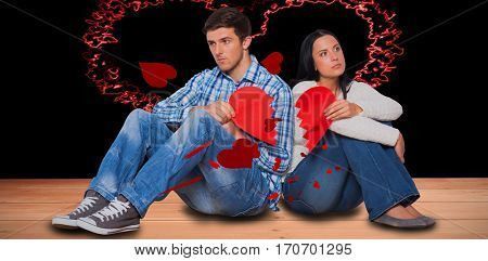 Young couple sitting on floor with broken heart against red love hearts