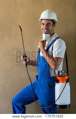 Portrait of happy manual worker with sprayer standing against wall