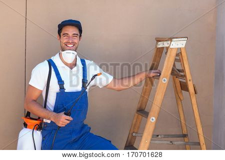 Portrait of pesticide worker standing by ladder against wall