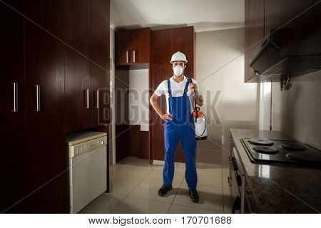 Portrait of pesticide worker standing with hand on hip in kitchen at home