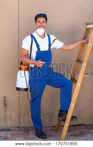 Portrait of man holding pesticide bottle while standing by ladder against wall
