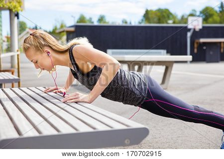 Full length side view of determined young woman doing pushups on bench in park