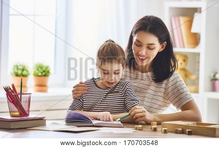 Pretty young mother and her cute daughter are reading a book. Learning to read at home.