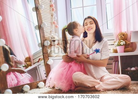 Happy loving family. Mother and her daughter in kids room. Funny mom and lovely child having fun indoors. Cute little girl is playing Princess fairy.