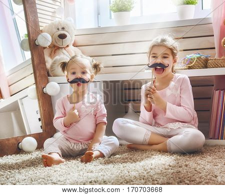 Funny family playing at home. Two cute little children girls with a paper accessories. Sisters are holding paper mustache on sticks.