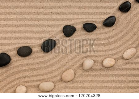 Two rows of stones lying on the sand with space for text. View from above