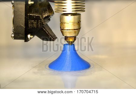 Modern 3D printer printing figure close-up macro.Automatic three dimensional 3d printer performs plastic blue colors modeling in laboratory. 3d-printing processing with white background