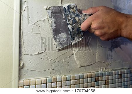 Repairs in the apartment: Install mosaic tiles: Spreading of tile adhesive with a trowel.