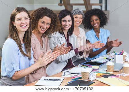 Portrait of interior designers applauding after listening to presentation in office